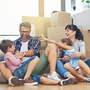 family sitting on floor of new home with packing boxes behind