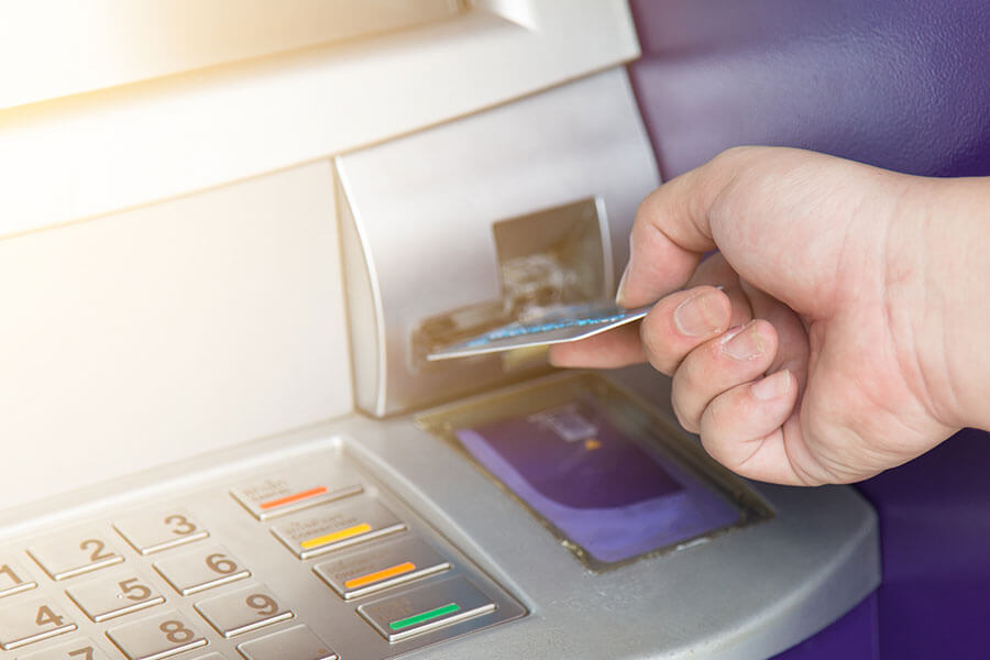 close up of person inserting debit card into an ATM