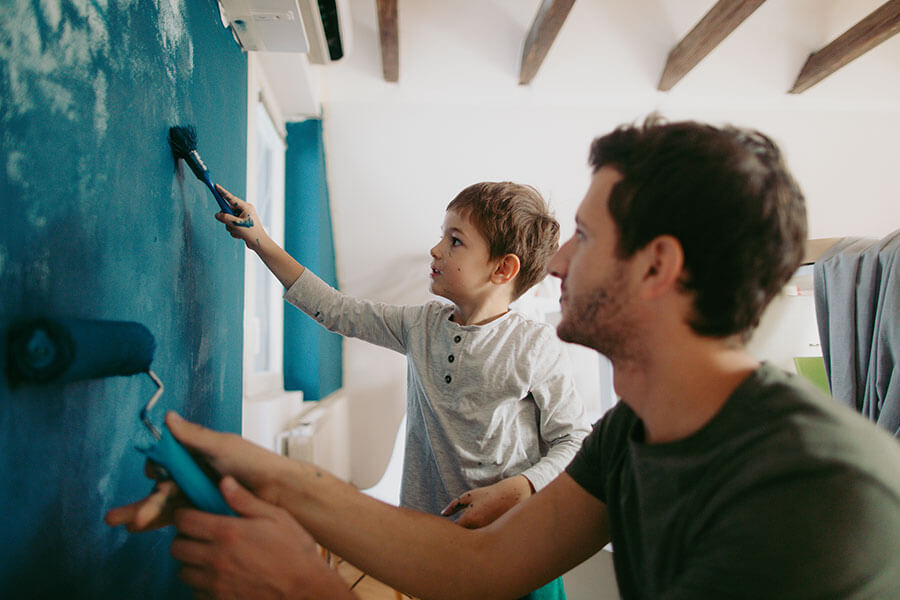 father and son painting a wall in home